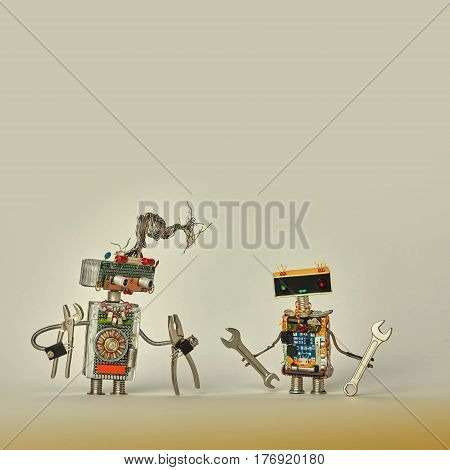 Construction workers service. Creative design toy robots with pliers hand wrench in arms. Colorful characters, wires, electronic circuit, chip capacitors resistors. Beige paper background copy space