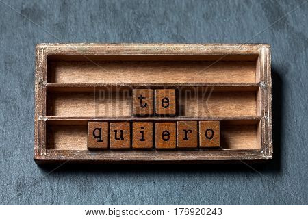 Te quiero. I love you in Spanish language. Vintage box, wooden cubes phrase with old style letters. Gray stone textured background. Close-up, up view, soft focus