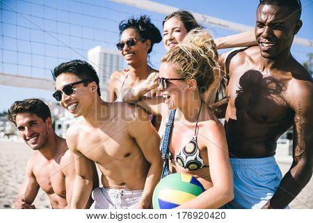 Group of friends playing beach volley on the beach and having fun