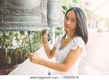 Thai woman visiting a buddhist temple with traditional bells