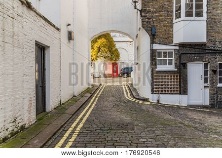 narrow alley with typical English buildings on the right side of the brick buildings on the left white buildings paving red telephone box
