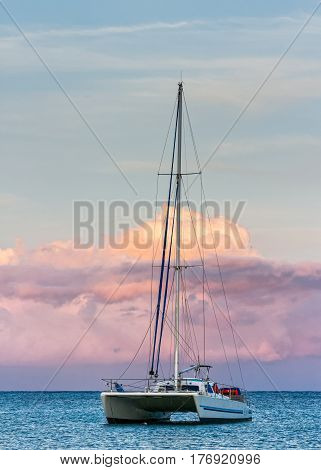 Catamaran anchored on the Hawaii coast with dramatic clouds in the distance.