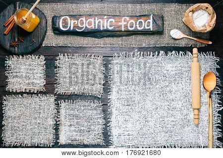 Rustic style template for food and drink industry. Burlap frames on dark wood background with flour pack, roller and honey. Wooden cutting boards and signboard with text 'Organic food' as title bar