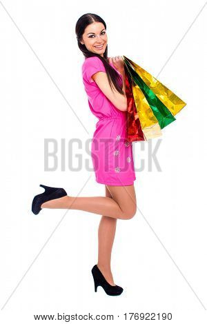 Young beautiful brunette woman in red dress with some shopping bags, isolated on white background