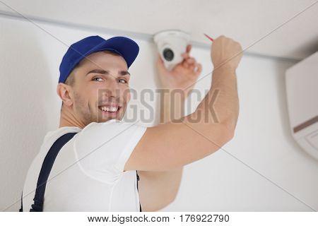 Technician fixing video surveillance camera