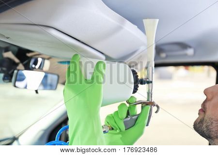 Handsome male cleaner removing dirt from car salon, close up
