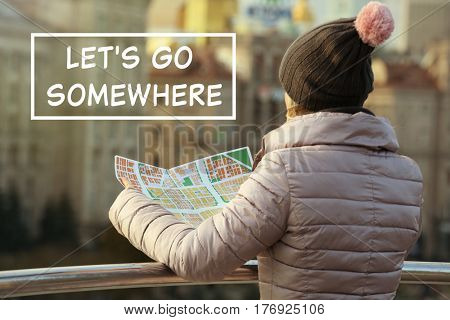 Woman holding map on street. Text LET'S GO SOMEWHERE on background