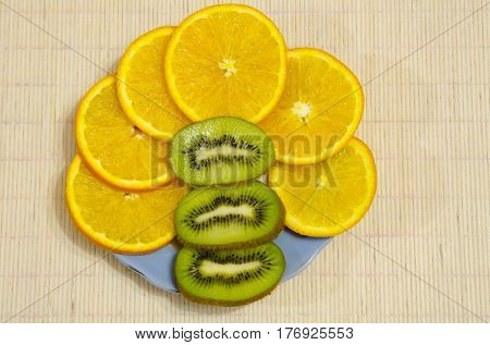 Cutting orange and kiwi lies on a plate.