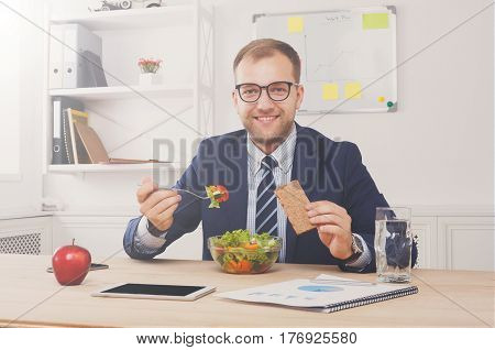 Man has healthy business lunch, vegetable salad, in modern office interior. Diet and eating right concept.