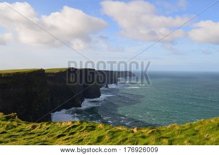 Ireland's lush green grass along the sea cliffs at the Cliffs of Moher in Ireland.