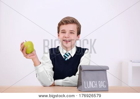 Cute schoolboy sitting at table with apple and lunch bag