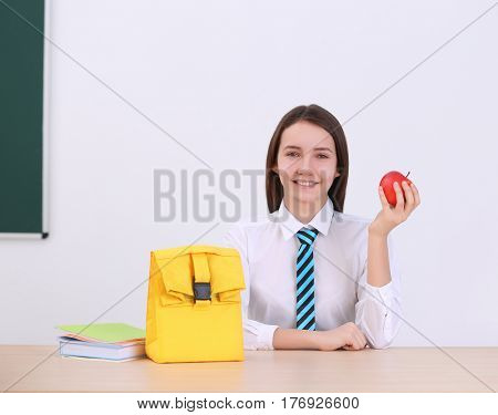 Cute schoolgirl with apple and lunch bag sitting at table in classroom