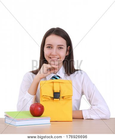 Cute schoolgirl with lunch bag sitting at table in classroom