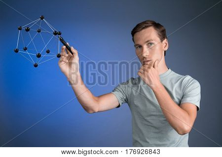 Young man works on a model of molecule.