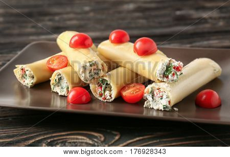 Delicious stuffed cannelloni with cherry tomatoes on wooden table