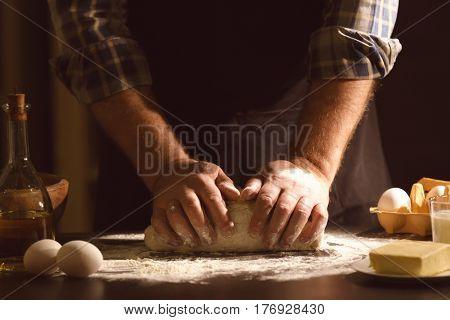 Man kneading dough in kitchen