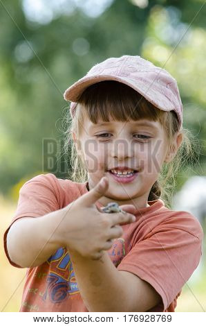 Dirty little girl caught a lizard on a farm