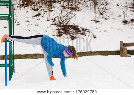 Outdoor sport exercises sporty outfit ideas. Woman wearing warm sportswear urban street training exercising outside during winter.
