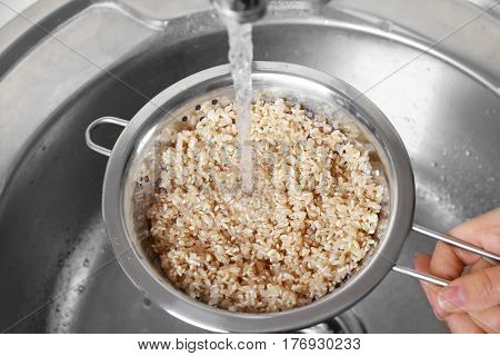 Washing raw brown rice in colander over kitchen sink