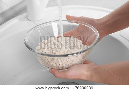 Woman rinsing rice in glass bowl under running water