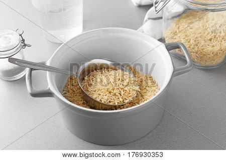 Saucepan with raw brown rice on table