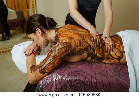 woman having health mud mask for body at spa-center. masseur hands massaging female back applying a medicinal mixture to the skin