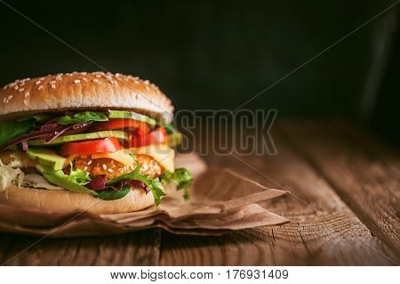 Delicious Fresh Homemade Burger With Chicken Nuggets And Avocado On A Wooden Table