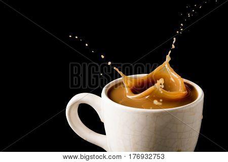Cup of splashing coffee on black background