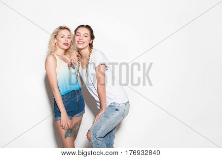 Portrait of two smiling pretty women. Horizontal studio shot.