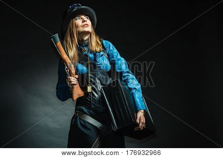 Steampunk subculture weapon threat concept. Vintage girl with gun. Young attractive lady in elegant outfit holding antique firearm.
