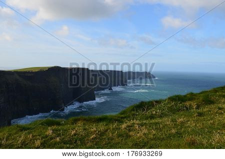 Thick green grass carpeting the top of the sea cliffs in County Clare Ireland.