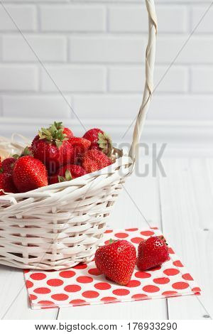 Ripe strawberry in the white basket with red polka-dot napkin on the white brick and wooden background vertical composition close-up view