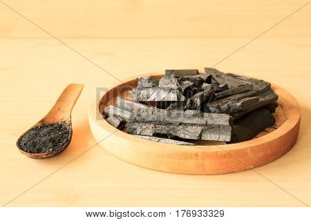 Charcoal and charcoal powder on wooden table background.