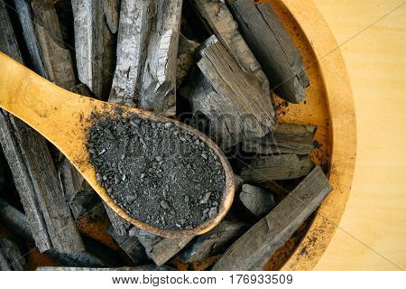Charcoal and charcoal powder on wooden spoon.