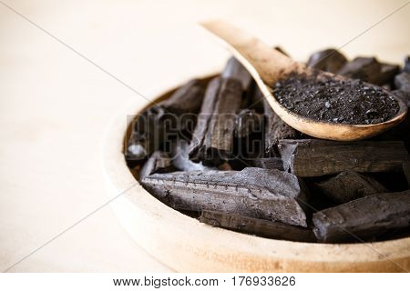 Charcoal and charcoal powder on wooden spoon. Selective focus