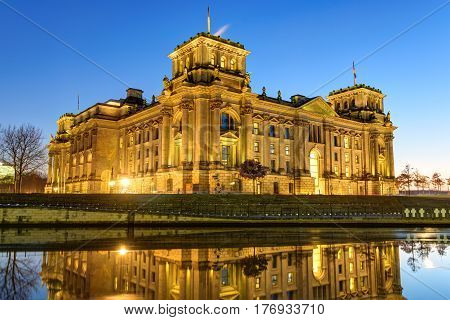 The famous Reichstag building at the river Spree in Berlin at night