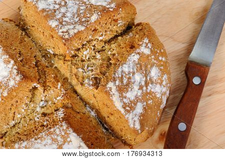 Newly-baked bread and a knife on a cutting board