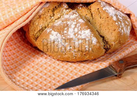 Newly-baked bread in a dishcloth and a knife