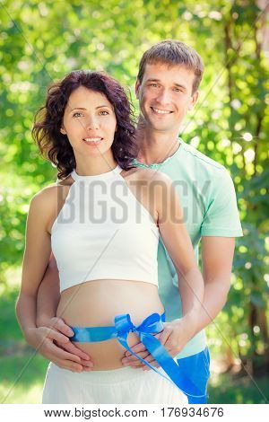 Happy man hugging belly of pregnant woman. Couple having fun outdoors in spring park. Mothers day concept