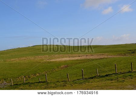 Green rolling hills and fields along the Cliff's of Moher in Ireland.