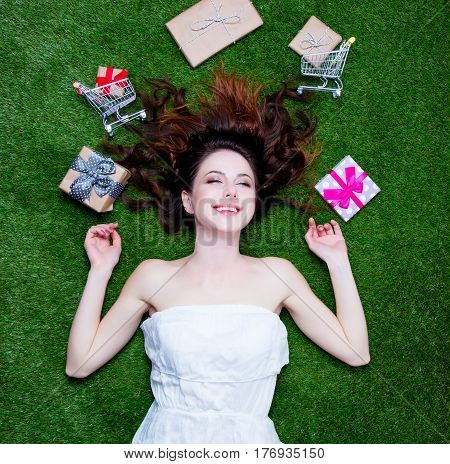 Beautiful Young Woman Near Gifts And Shopping Carts Lying On The Wonderful Green Grass Background