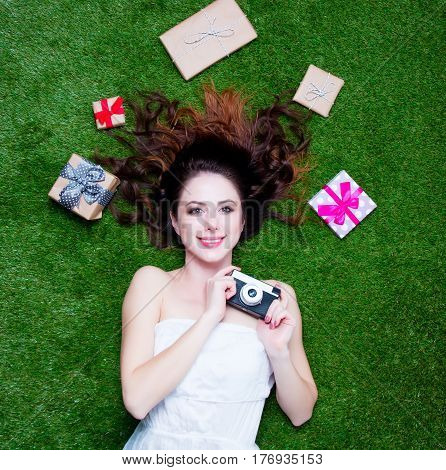 Beautiful Young Woman Near Gifts  Lying With Camera On The Wonderful Green Grass Background
