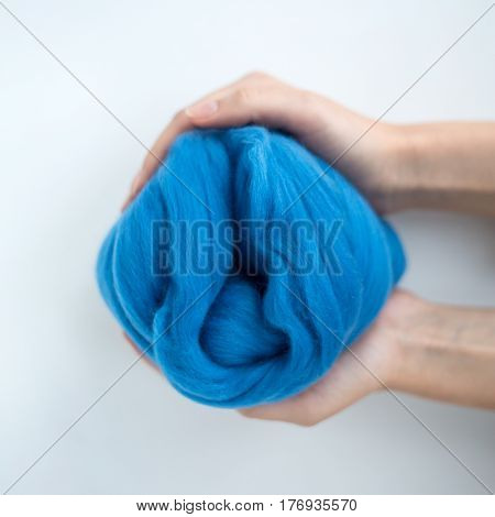 Close-up of blue merino wool ball in hands.