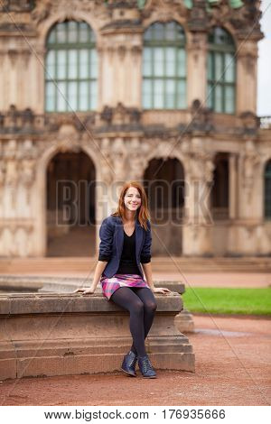 Beautiful Young Woman Sitting On The Fountain Near Wonderful Building