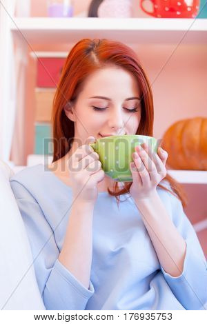 Photo Of Beautiful Young Woman Drinking Her Fresh Coffee And Relaxing On The Sofa