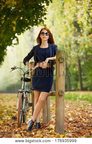 Beautiful Young Woman Standing Near Wooden Fence With Bicycle In The Park