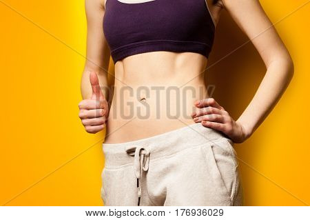 photo of perfect slim female body on the wonderful yellow background