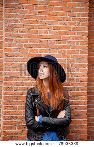 beautiful young woman standing near the bricks building wall