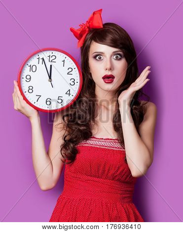 photo of beautiful young woman with clock on the wonderful purple background
