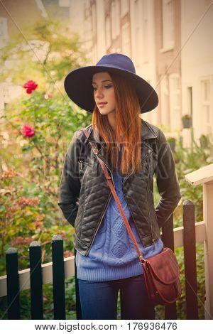 beautiful young woman standing near the garden